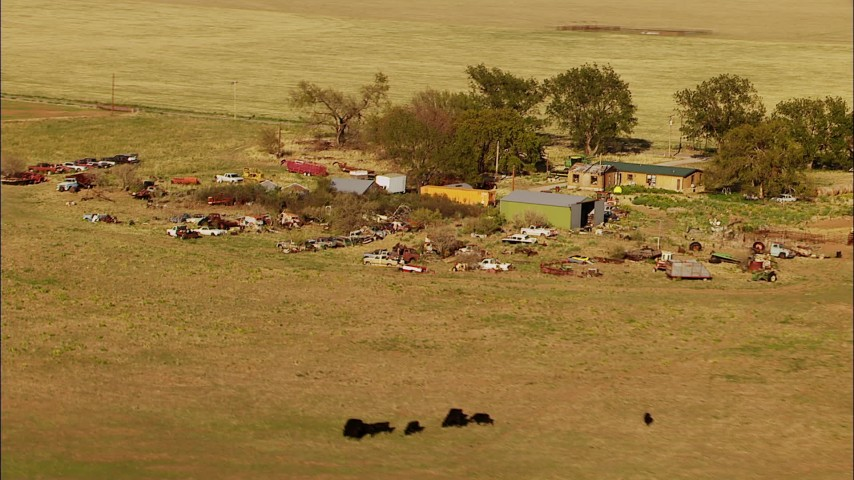 1080 stock footage aerial video fly over fields to approach grazing cattle and junkyard by rural home in Oklahoma Aerial Stock Footage | HDA12_114
