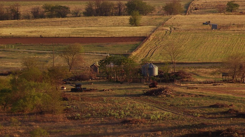 1080 stock footage aerial video of a barn, silos, equipment beside a country road at sunset in Oklahoma Aerial Stock Footage | HDA12_136
