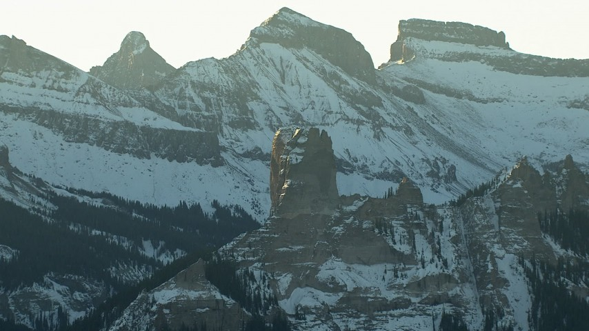 HD stock footage aerial video of snowy Rocky Mountains and a rock formation at sunrise, Colorado Aerial Stock Footage   HDA13_403_03