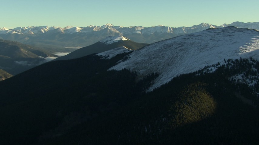 HD stock footage aerial video of panning across a snowy ridge at sunrise, Rocky Mountains, Colorado Aerial Stock Footage   HDA13_440