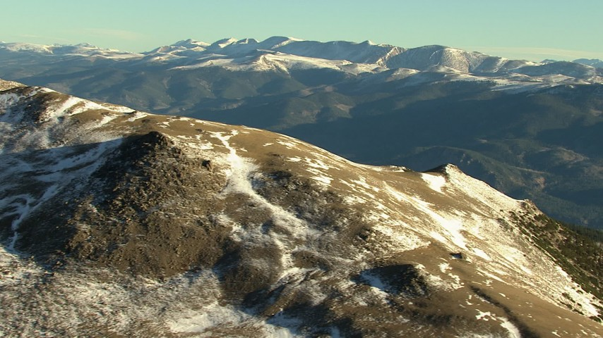 HD stock footage aerial video of a mountain summit with snow at sunrise, zoom to wider view of Rocky Mountains, Colorado Aerial Stock Footage | HDA13_450