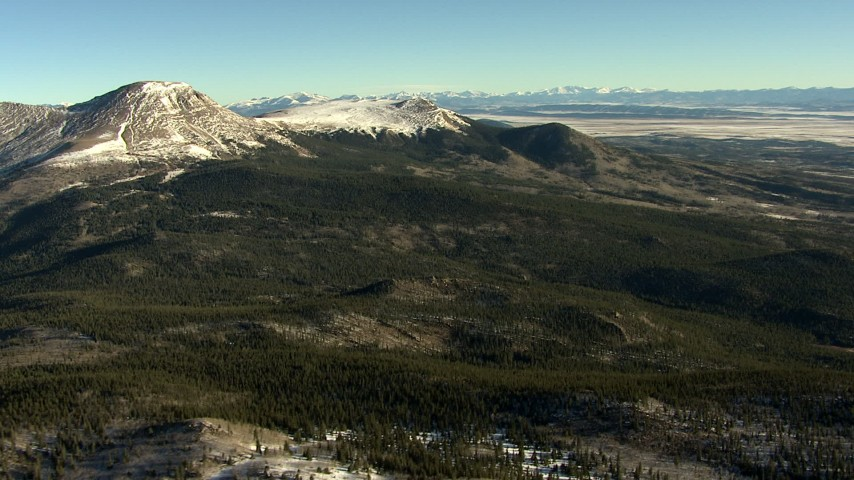 HD stock footage aerial video of snowy mountains and green hills at sunrise in the Rocky Mountains, Colorado Aerial Stock Footage | HDA13_455