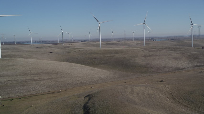 5K stock footage aerial video tilt from hills to reveal Shiloh Wind Power Plant windmills, Montezuma Hills, California Aerial Stock Footage | JDC01_065