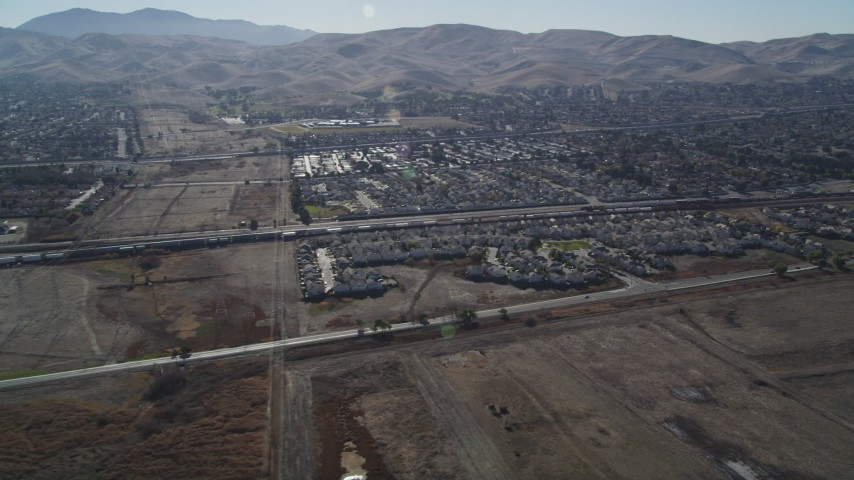 5K stock footage aerial video of approaching a train passing suburban houses, Pittsburg, California Aerial Stock Footage | JDC01_083