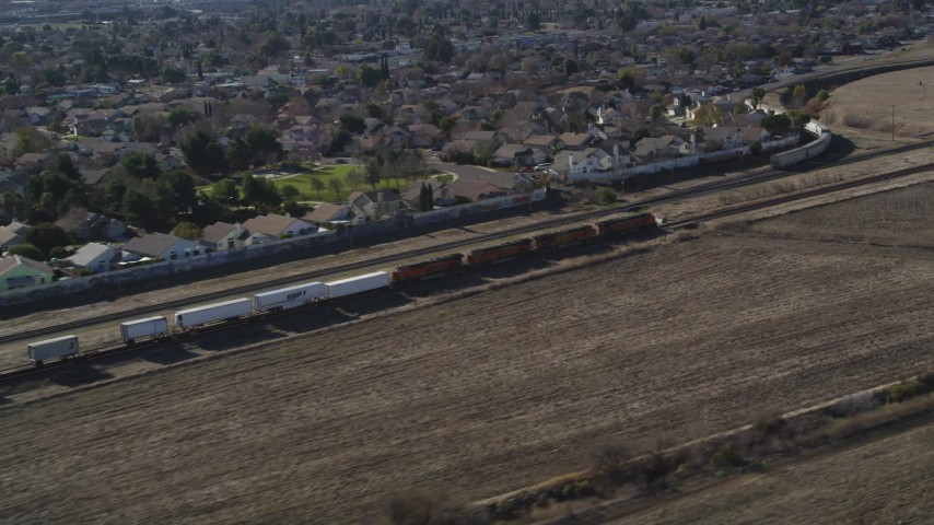 5K stock footage aerial video of tracking train traveling by suburban area, fields, Pittsburg, California Aerial Stock Footage | JDC01_084