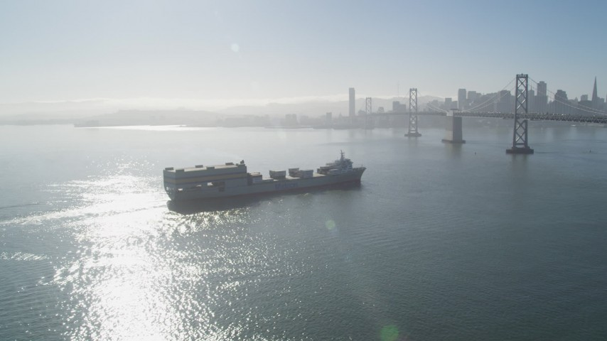 5K aerial video of flying by a cargo ship approaching Bay Bridge, San Francisco, California Aerial Stock Footage | JDC02_042
