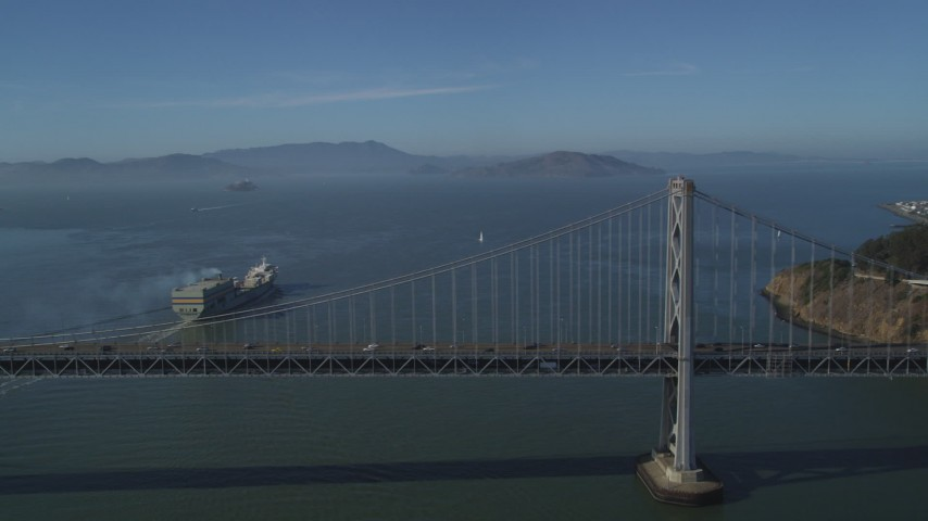 5K stock footage aerial video of flying by a cargo ship sailing away from Bay Bridge, San Francisco, California Aerial Stock Footage | JDC02_043