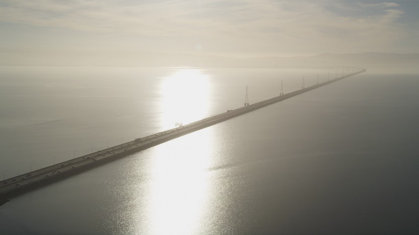 5K stock footage aerial video of flying by San Mateo Bridge, sun reflecting off San Francisco Bay, California Aerial Stock Footage | JDC04_040