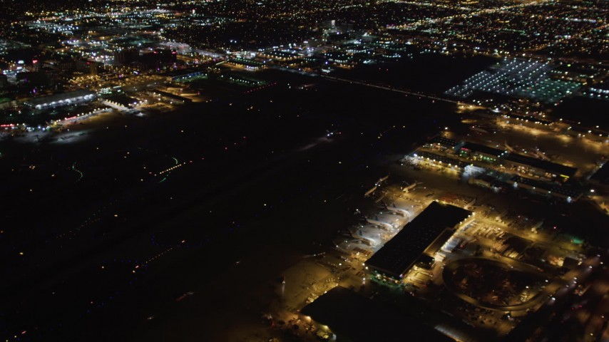 5K stock footage aerial video track a jet landing at night, LAX (Los Angeles International Airport), California Aerial Stock Footage | LD01_0007