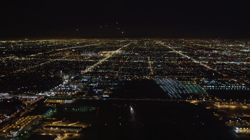 5K stock footage aerial video tilt from runway to reveal approaching jet at night, LAX (Los Angeles International Airport), California Aerial Stock Footage | LD01_0008