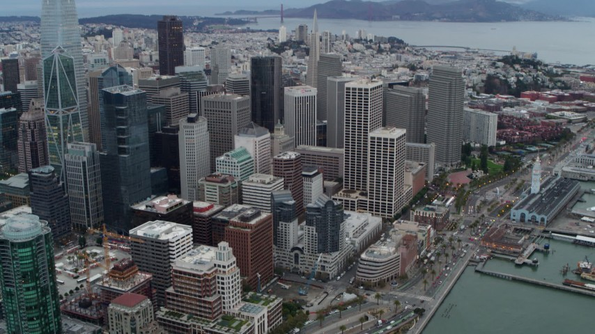 5.7K stock footage aerial video tilt from skyscrapers in Downtown San Francisco, California to reveal Embarcadero and Bay Bridge Aerial Stock Footage | PP0002_000041