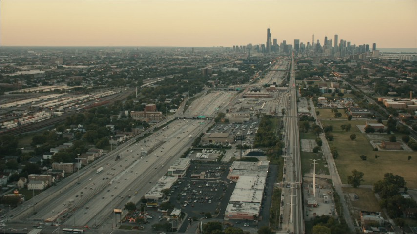 HD stock footage aerial video follow freeway and rail through South Side at sunset toward Downtown Chicago, Illinois Aerial Stock Footage | PP001_020