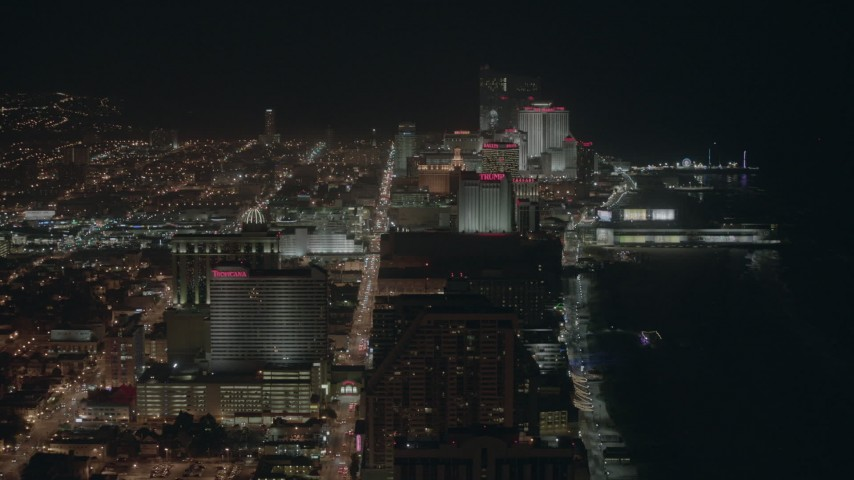 HD stock footage aerial video of flying by hotels and casinos on the shore at night Atlantic City, New Jersey Aerial Stock Footage | PP003_017