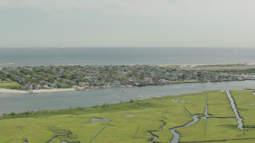 HD stock footage aerial video of a coastal community across a channel and marshes, Point Lookout, New York Aerial Stock Footage | PP003_049