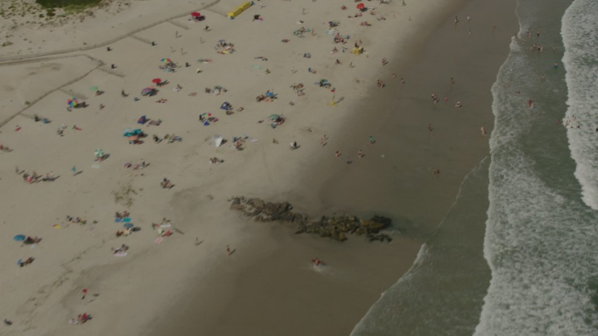 HD stock footage aerial video of a reverse view of sunbathers on the beach in Long Beach, New York Aerial Stock Footage | PP003_054