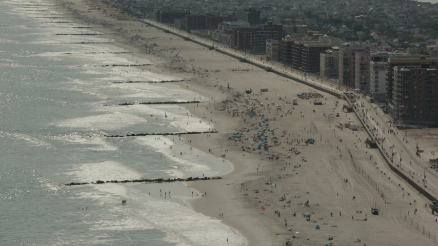 HD stock footage aerial video of beach-goers near the boardwalk in Long Beach, New York Aerial Stock Footage | PP003_055