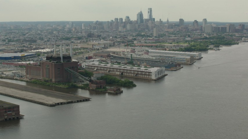 HD stock footage aerial video flyby piers and riverfront factory with a view of the Downtown Philadelphia skyline, Pennsylvania Aerial Stock Footage | PP003_089