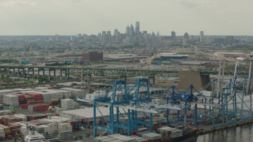 HD stock footage aerial video of containers and cranes at a shipping port, with a view of Downtown Philadelphia skyline, Pennsylvania Aerial Stock Footage | PP003_091