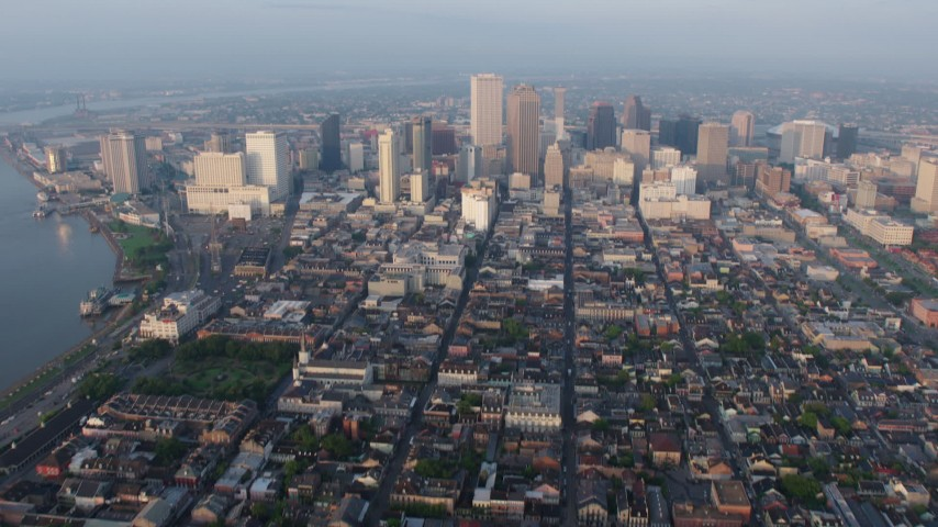 4K aerial  video of tilt from French Quarter streets to reveal and approach Downtown at sunrise, New Orleans, Louisiana Aerial Stock Footage | PVED01_006