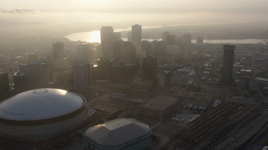 4K stock footage aerial video tilt to reveal Superdome and Downtown New Orleans skyscrapers at sunrise, Louisiana Aerial Stock Footage | PVED01_009