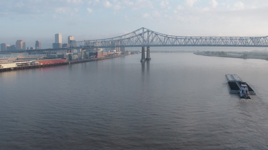 4K aerial video tilt to reveal barge near the Crescent City Connection Bridge at sunrise, New Orleans, Louisiana Aerial Stock Footage | PVED01_020