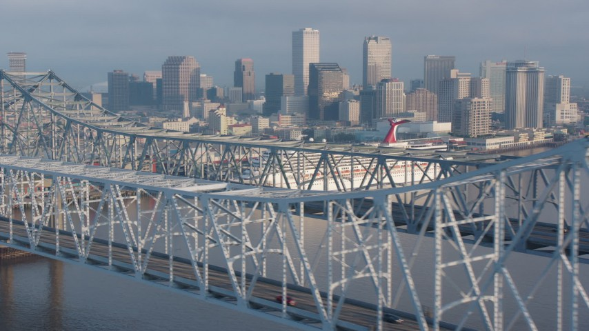 4K aerial video flyby Crescent City Connection Bridge and reveal Downtown New Orleans skyline at sunrise, Louisiana Aerial Stock Footage | PVED01_046