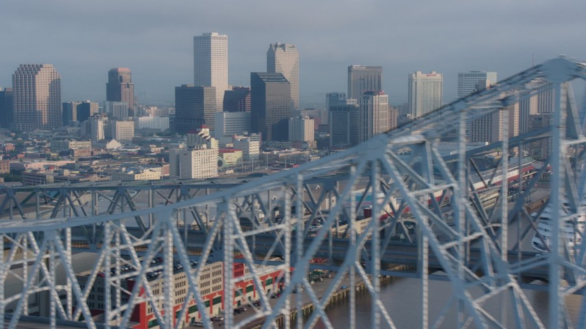 4K stock footage aerial video flyby the Crescent City Connection Bridge, reveal Downtown New Orleans skyline at sunrise, Louisiana Aerial Stock Footage | PVED01_047