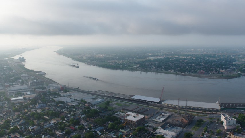 4K aerial video of a wide orbit of barges on the Mississippi River by the French Quarter of New Orleans at sunrise, Louisiana Aerial Stock Footage | PVED01_057