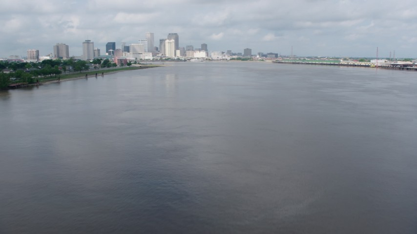 4K stock footage aerial video fly low over Mississippi River to approach Downtown New Orleans skyline, Louisiana Aerial Stock Footage | PVED01_128