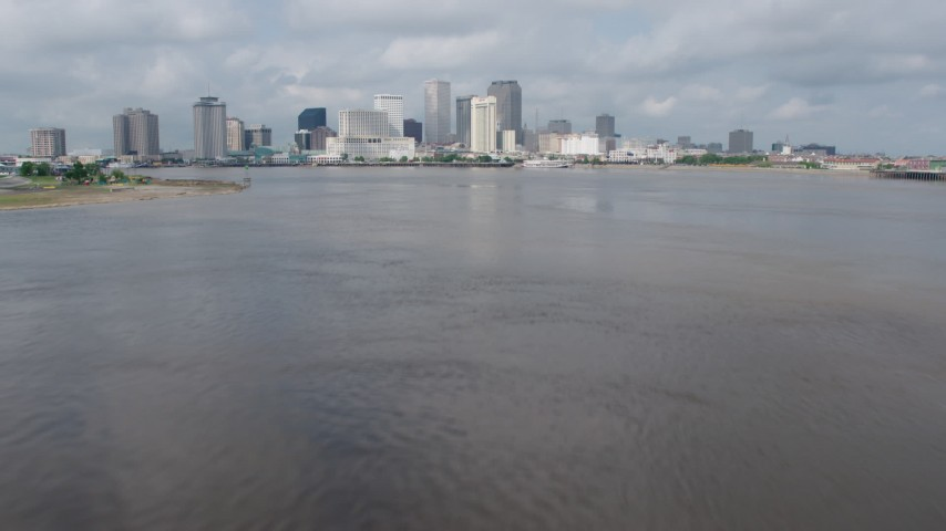 4K aerial video tilt to reveal Downtown New Orleans skyline while flying over Mississippi River, Louisiana Aerial Stock Footage | PVED01_129