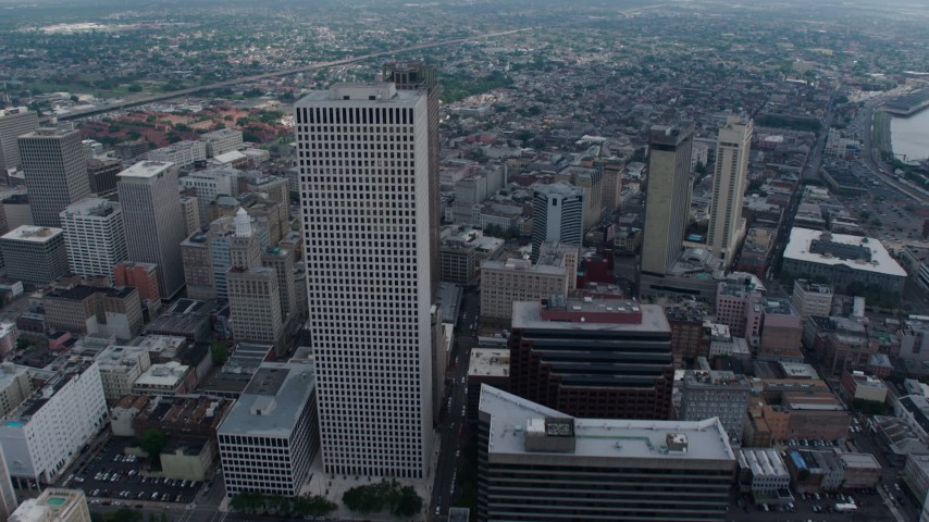 4K aerial video tilt to reveal and fly over Downtown New Orleans skyscrapers toward French Quarter, Louisiana Aerial Stock Footage | PVED01_140