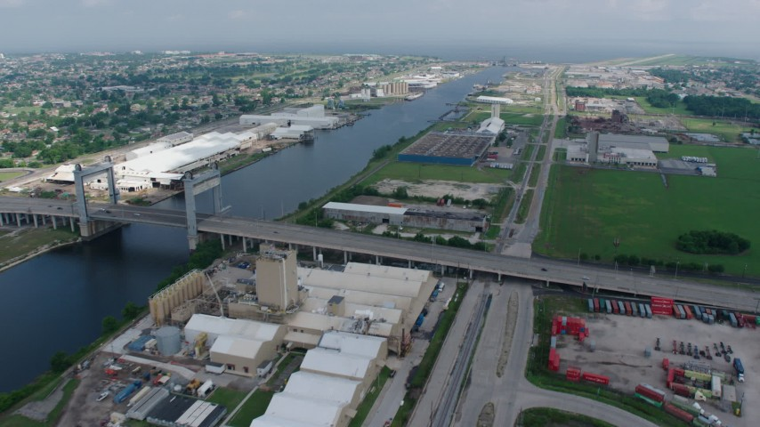 4K stock footage aerial video flyby small bridge and factory buildings on the shore of Industrial Canal in New Orleans East, Louisiana Aerial Stock Footage | PVED01_168