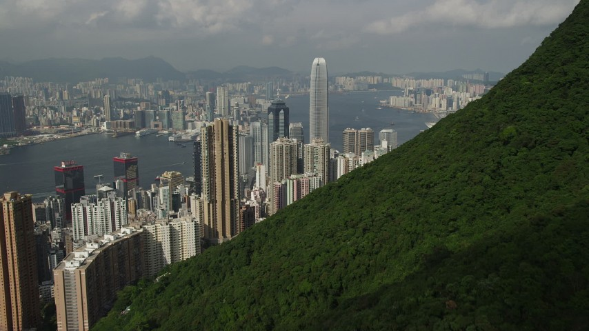 5K stock footage aerial video fly over green mountain to approach Hong Kong Island skyscrapers, China Aerial Stock Footage | SS01_0036