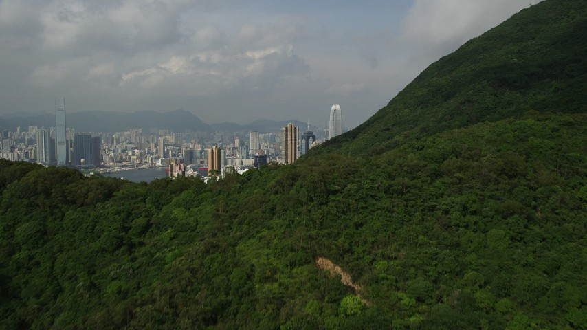 5K stock footage aerial video fly over forest and mountain to reveal skyscrapers on Hong Kong Island, China Aerial Stock Footage | SS01_0038