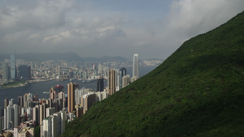 5K stock footage aerial video approach skyscrapers on Hong Kong Island from green mountains, China Aerial Stock Footage | SS01_0039