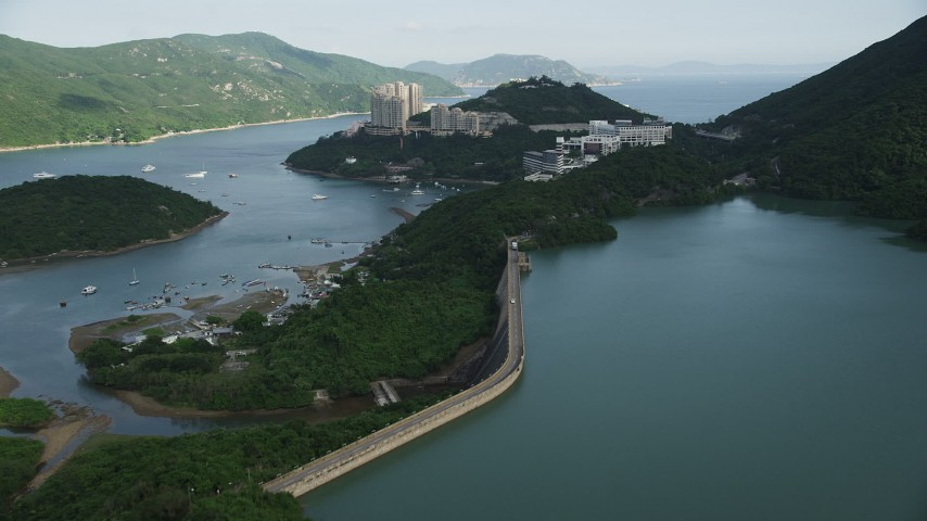 5K stock footage aerial video fly over dam and reservoir to approach harbor-side apartment buildings on Hong Kong Island, China Aerial Stock Footage | SS01_0065