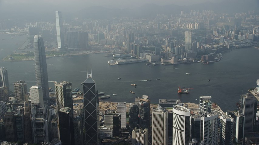 5K stock footage aerial video approach harbor from Hong Kong Island and pan across the water and Kowloon shoreline, China Aerial Stock Footage | SS01_0083