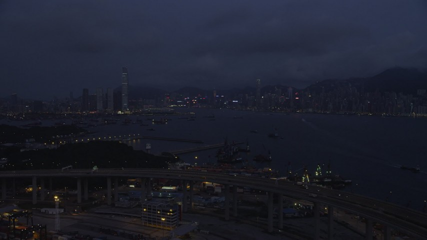 Approach Kowloon and Hong Kong Island Skylines from the Port of Hong Kong at Night Aerial Stock Footage | SS01_0120