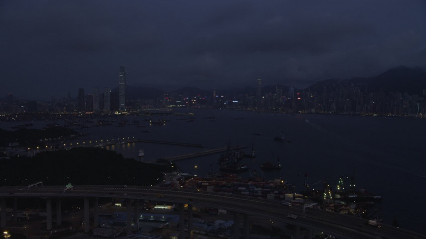 5K stock footage aerial video approach Kowloon and Hong Kong Island skylines from the Port of Hong Kong at night, China Aerial Stock Footage | SS01_0120