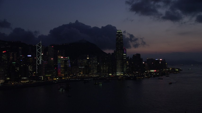 5K stock footage aerial video of Hong Kong Island skyline seen from Victoria Harbor at nighttime, China Aerial Stock Footage | SS01_0144