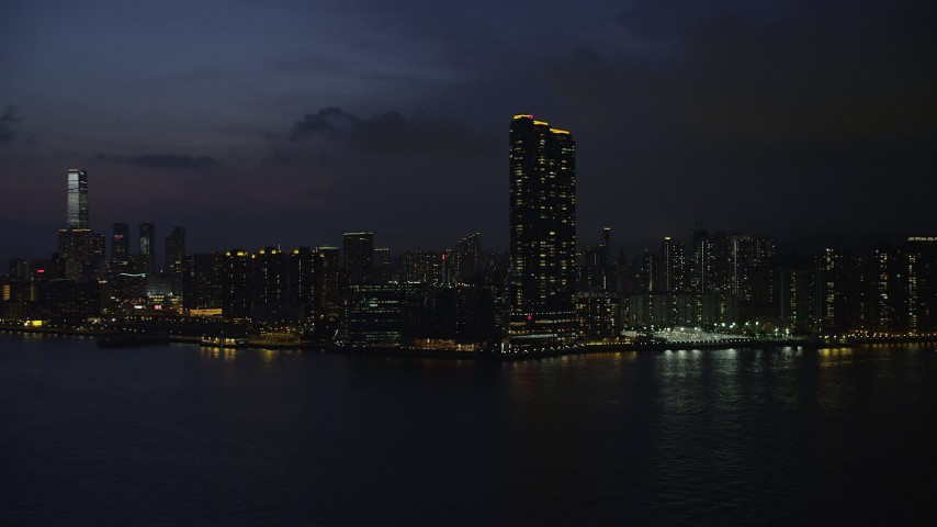 5K stock footage aerial video approach Kowloon skyscraper overlooking Victoria Harbor at night, Hong Kong, China Aerial Stock Footage | SS01_0157