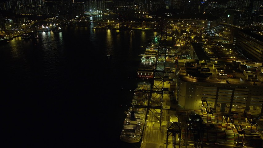 Fly Over a Row of Cargo Ships Docked at the Port of Hong Kong at Nighttime Aerial Stock Footage | SS01_0237