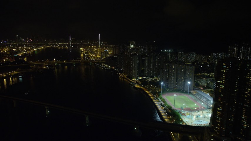 5K stock footage aerial video approach Stonecutters Bridge from waterfront apartment complexes on Tsing Yi Island at night, China Aerial Stock Footage | SS01_0258