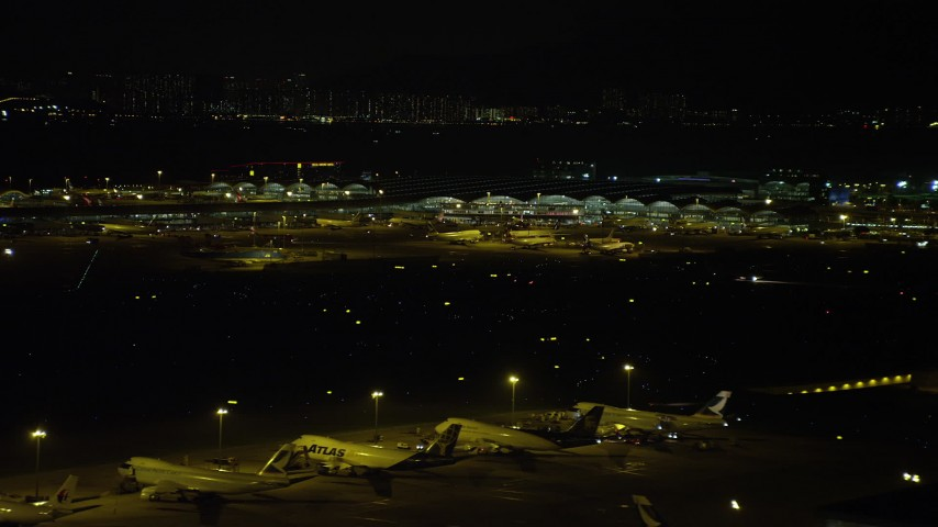 5K stock footage aerial video of Hong Kong International Airport Terminals at night, and tilt to parked airliners, China Aerial Stock Footage | SS01_0280