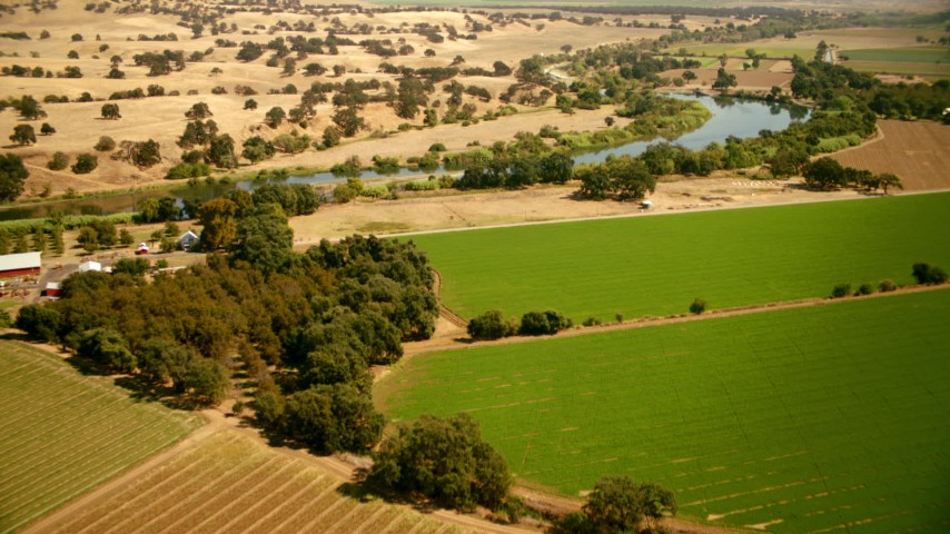 1080 stock footage aerial video of flying over farmland and house toward the river in Capay, California Aerial Stock Footage | TS01_266