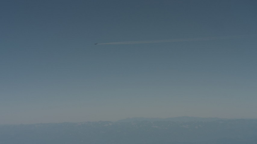 4K stock footage aerial video air-to-air view of a jet airplane contrail flying over mountains in Solano County, California Aerial Stock Footage | WA001_029