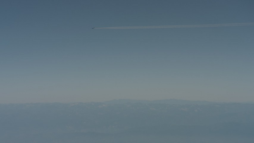 4K stock footage aerial video air-to-air of a jet airplane contrail over mountains in the distance, Solano County, California Aerial Stock Footage | WA001_030