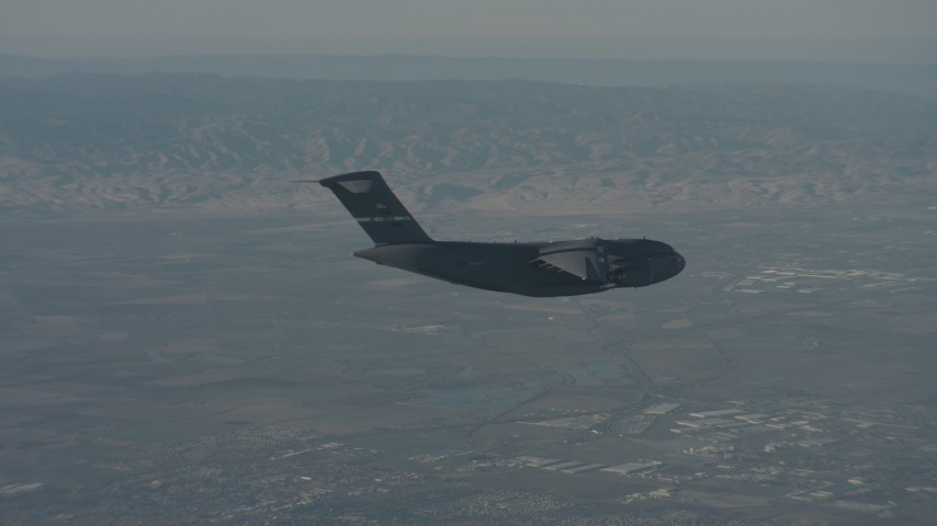 Zoom in on a Boeing C-17 flying over Solano County, California Aerial Stock Footage | WA001_043