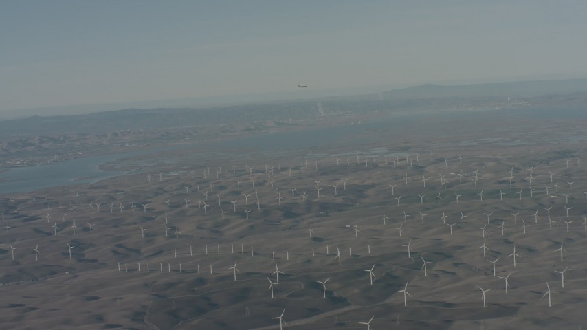 4K stock footage aerial video air-to-air view of a jet flying near Suisun Bay and windmills in Solano County, California Aerial Stock Footage | WA001_050