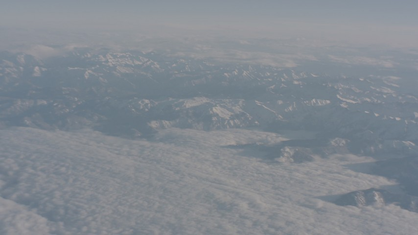 4K stock footage aerial video pan across a blanket of clouds and snowy Sierra Nevada Mountains, California Aerial Stock Footage | WA002_033